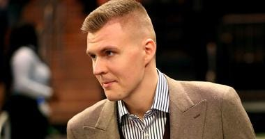 Kristaps Porzingis looks on in street clothes during a New York Knicks game.