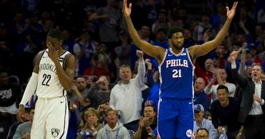Joel Embiid of the Philadelphia 76ers tries to pump up the crowd while the Brooklyn Nets' Caris LeVert looks away during Game 2 of the first round of the NBA playoffs.