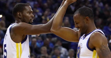 Kevin Durant #35 of the Golden State Warriors high fives Andre Iguodala #9 during their game against the Phoenix Suns at ORACLE Arena on October 22, 2018 in Oakland, California.