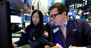 Specialist Vera Liu, left, and trader James Matthews work on the floor of the New York Stock Exchange, Wednesday, Dec. 26, 2018