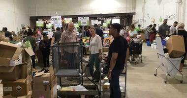 Teachers browse the free selection at a school supply giveaway Saturday, August 25.