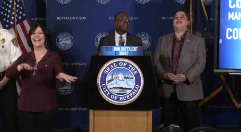 Karen Gambino (left) provides sign language interpreting during Mayor Byron Brown's March 17 press conference. In this moment, Mayor Brown encouraged Buffalonians to celebrate Tom Brady leaving New England. March 28, 2020 (Photo via Mayor Brown Facebook)