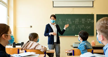 Teacher in a classroom with covid safety measures in place