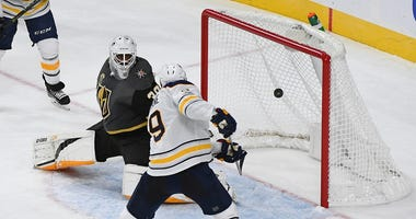 Oct 17, 2017; Las Vegas, NV, USA; Buffalo Sabres left wing Evander Kane (9) bats a puck out of the air past Vegas Golden Knights goalie Malcolm Subban (30) to tie the game late in the third period of a game at T-Mobile Arena.