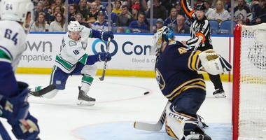 Jake Virtanen #18 of the Vancouver Canucks scores a goal on a one-timer past goaltender Carter Hutton #40 of the Buffalo Sabres
