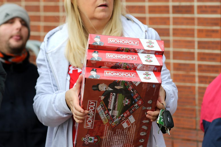 Woman carrying Monopoly games