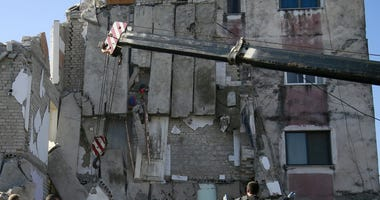 Rescuers search at a damaged building after a magnitude 6.4 earthquake in Thumane, western Albania, Tuesday, Nov. 26, 2019.