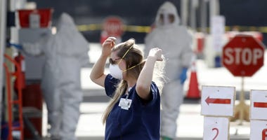 Medical University of South Carolina project manager Amy Jackson adjusts her face mask as healthcare providers dress in protective suiting