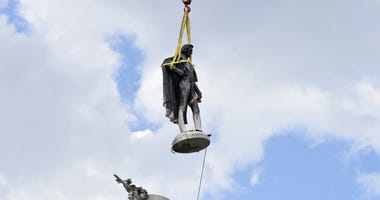 The statue of former U.S. vice president and slavery advocate John C. Calhoun hovers above its monument after contractors completed a 17-hour removal process on Wednesday, June 24, 2020.
