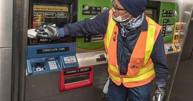 An employee cleaning an MTA ticket machine