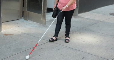 Visually impaired person using a cane
