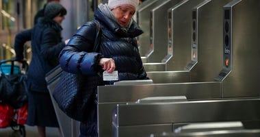 A customer swipes her metro card