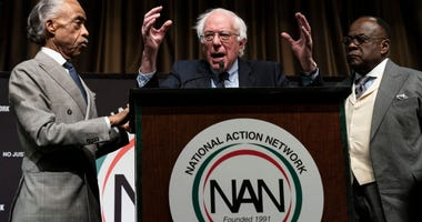 Flanked by Rev. Al Sharpton (L) and Rev. W. Franklyn Richardson (R) look on as Democratic presidential candidate U.S. Sen. Bernie Sanders (I-VT) speaks at the National Action Network's annual convention, April 5, 2019 in New York City.