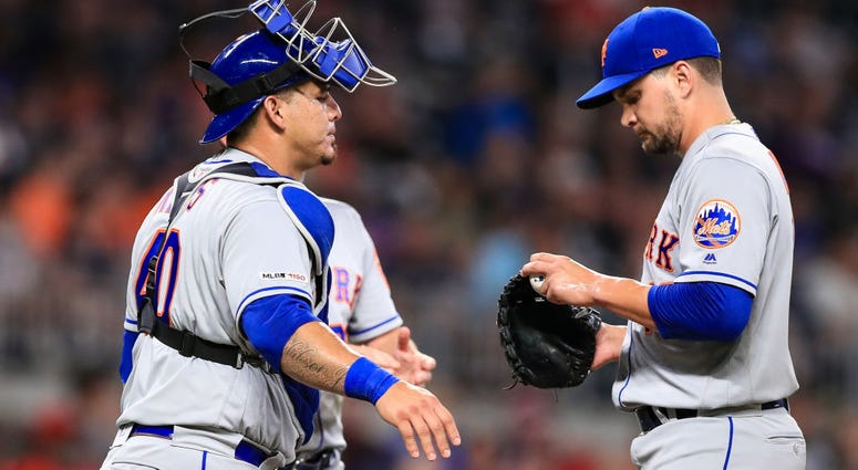 Wilson Ramos #40 speaks with Luis Avilan #43 of the New York Mets in the seventh inning during the game against the Atlanta Braves at SunTrust Park on August 13, 2019