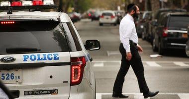 Hasidic man walking by police car in Brooklyn