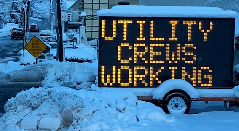 Utility crews working sign