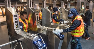 MTA workers cleaning the subway turnstiles