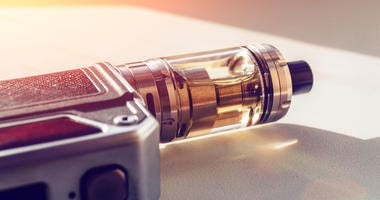 Modern vape device: electric box mod on dna chip and tank with vaping liquid in sun light
