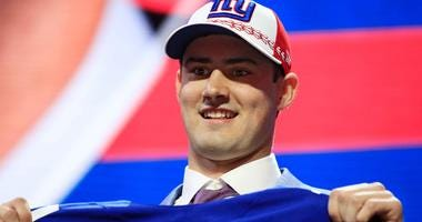 Daniel Jones holds up his New York Giants jersey at the 2019 NFL Draft.