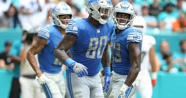 Michael Roberts celebrates a touchdown with his Lions teammates.