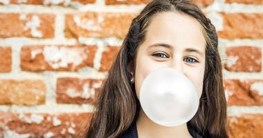 Little Happy Girl Blowing a Chewing Gum over a Brick Wall