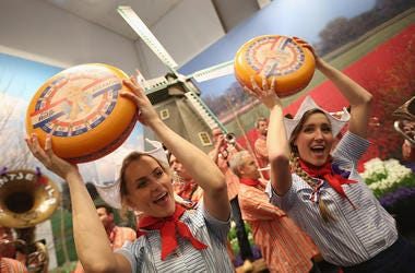 Women holding cheese wheels
