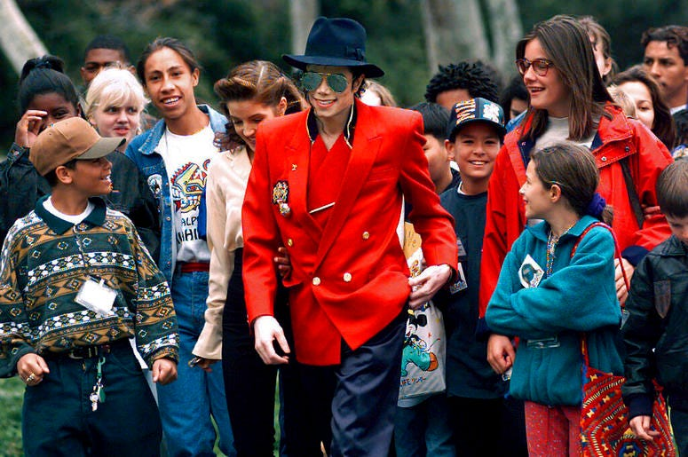 Michael Jackson and Lisa Marie Presley, behind him at left, walk with children that were invited guests at his Neverland Ranch