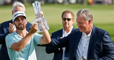 Jul 7, 2019; Blaine, MN, USA; Matthew Wolff takes the trophy from 3M vice president Jeff Lavers after winning the 3M Championship golf tournament at TPC Twin Cities.