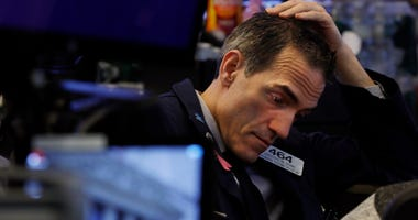 rader Gregory Rowe prepares for the day's activity on the floor of the New York Stock Exchange, Monday, March 9, 2020. Trading in Wall Street futures has been halted after they fell by more than the daily limit of 5%.