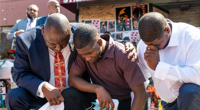 Quincy Mason Floyd (C), son of George Floyd, and attorney Ben Crump (L) kneel at the site where Floyd was killed on June 3, 2020 in Minneapolis, Minnesota.