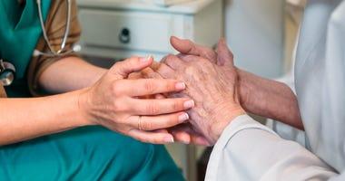 Doctor giving encouragement to elderly patient - stock photo