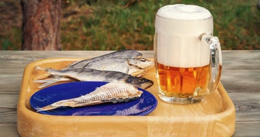 Mug of light beer and dried fish on a wooden table in a summer day outdoors