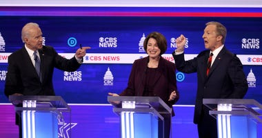 Joe Biden (L) and Tom Steyer (R) debate as Sen. Amy Klobuchar (D-MN) reacts