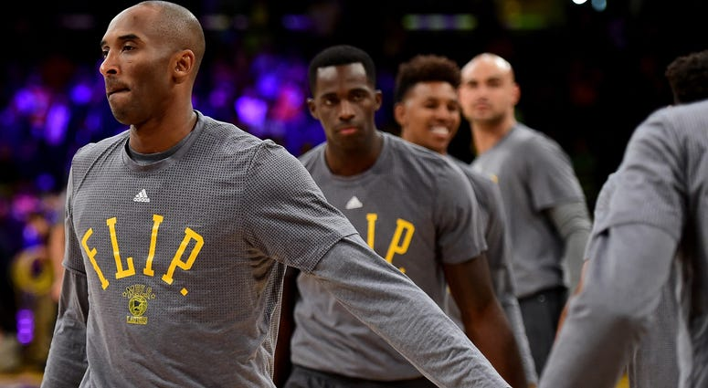 """Kobe Bryant #24 of the Los Angeles Lakers and the Los Angeles Lakers team wear t-shirts to honor the passing of Philip """"Flip"""" Saunders before the game against the Minnesota Timberwolves at Staples Center on October 28, 2015 in Los Angeles, California."""