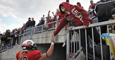 A young fan congratulates St. Cloud State University players as they leave the field after a game in 2014
