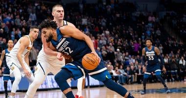 Karl-Anthony Towns drives on Nikola Jokic of the Nuggets