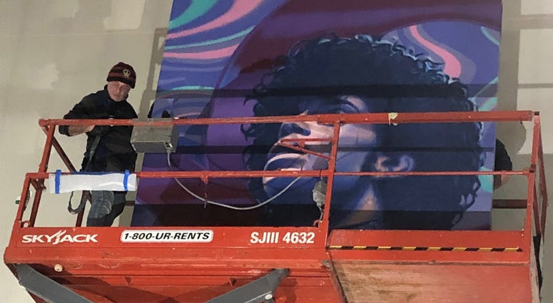 A mural of Prince being installed at MSP