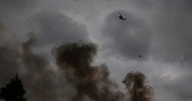 : A helicpter water bombs a fire at Voyager Point in western Sydney on January 05, 2020 in Sydney, Australia.