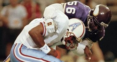 In this Aug. 27, 1990, file photo, Minnesota Vikings linebacker Chris Doleman (56) brings down Houston Oilers quarterback Warren Moon for a safety during preseason NFL football action in Minneapolis.