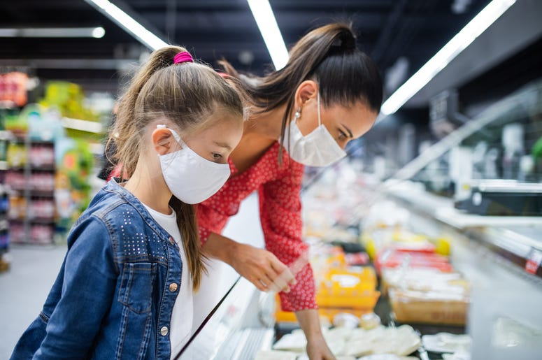 Woman and Child Masked Choosing Groceries