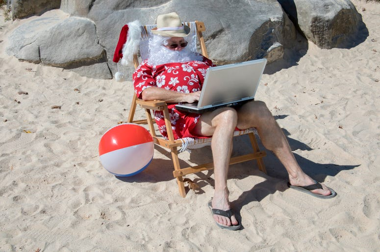 Santa Claus working on beach with laptop computer
