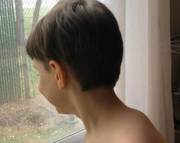 Child Looking Out Of Window At Hail. LDG