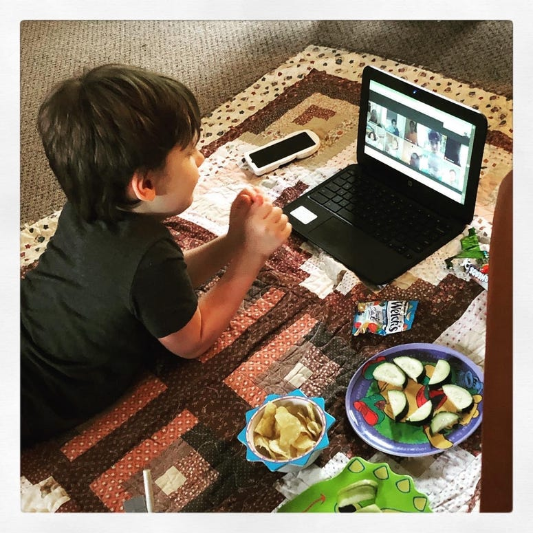 Child doing online learning with indoor picnic