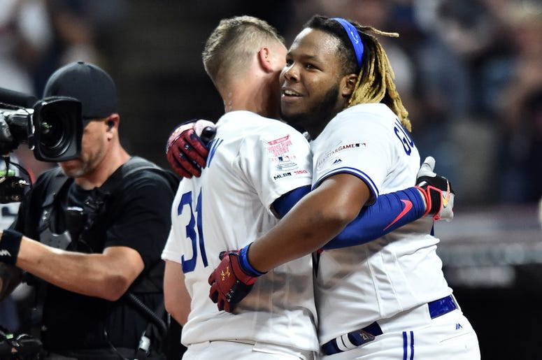 Los Angeles Dodgers outfielder Joc Pederson (31) and Toronto Blue Jays third baseman Vladimir Guerrero Jr. (27) hug after the second round overtime in the 2019 MLB Home Run Derby at Progressive Field.