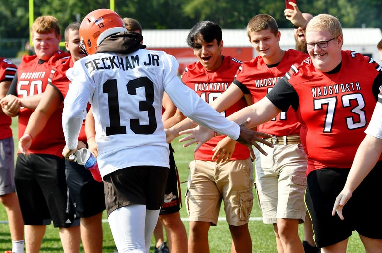 Cleveland Browns wide receiver Odell Beckham (13) slaps hands with the Wadsworth High School football team as he enters the field during training camp at the Cleveland Browns Training Complex.
