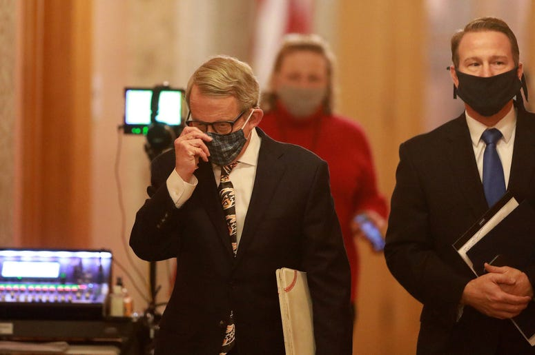 Ohio Gov. Mike DeWine (left) and Lt. Gov. Jon Husted wear their masks while walking into the daily coronavirus news conference on Friday, April 17, 2020 at the Ohio Statehouse in Columbus, Ohio. ghows-OH-200619928-11c6f288.jpg
