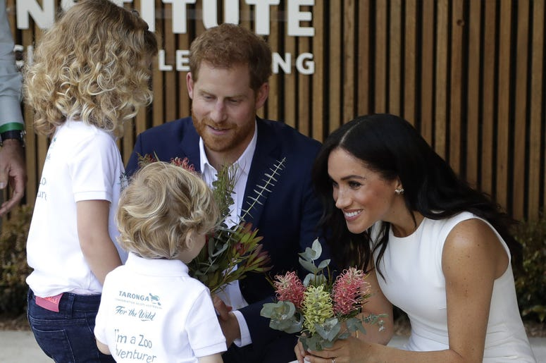 The Duke and Duchess of Sussex receive native flowers from Finley Blue and Dasha Gallagher, left, at Taronga Zoo in Sydney, Australia.