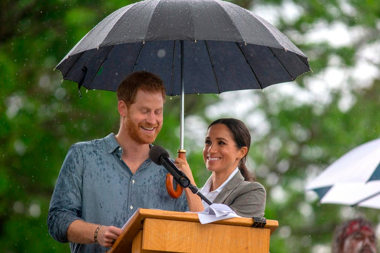 he Duchess of Sussex holds an umbrella as the Duke of Sussex makes a speech at a community picnic in Victoria Park in Dubbo, New South Wales, on the second day of the royal couple's visit to Australia
