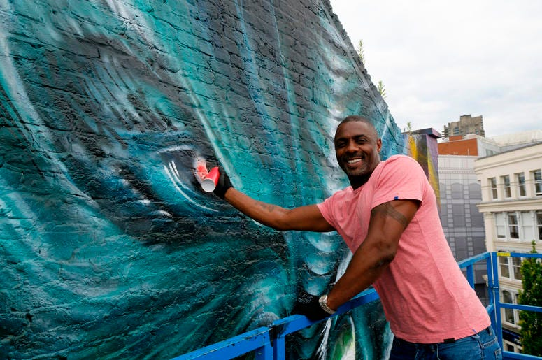 """Idris Elba paints in the eye of his character """"Krall"""" during the unveiling of a Star Trek Beyond mural by artist Jim Vision in Clerkenwell, London."""