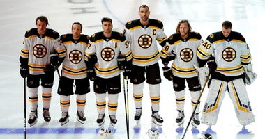 The Boston Bruins link arms during the national anthem